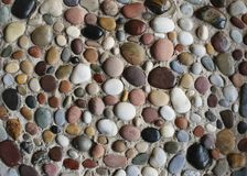 Sea pebbles in the sand. Colorful sea pebbles royalty free stock images