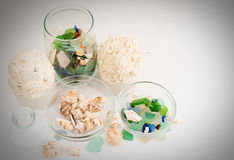 Sea pebbles and shells in glass containers royalty free stock photos