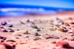 Sea pebbles, stones and rocks, laying on beach sand. Macro shot of magical, healing, warm sea pebbles, stones and rocks, laying on beach sand. Ocean waves Stock Image
