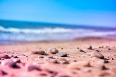 Sea pebbles, stones and rocks, laying on beach sand. Macro shot of magical, healing, warm sea pebbles, stones and rocks, laying on beach sand. Ocean waves Royalty Free Stock Photography