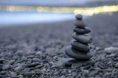 Sea pebbles tower closeup. At dusk against city ligths. Shot taken at French Riviera, Mediterranean sea Stock Photography