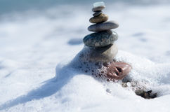 Sea pebbles tower closeup. Pebbles sculpture made on Barcelona beach. Foamy wave is trying to destroy sculpture Stock Photography