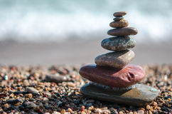 Sea pebbles tower closeup. Pebbles sculpture made on Barcelona beach. Mediterranean sea against the background Royalty Free Stock Image