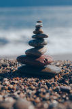 Sea pebbles tower closeup. Pebbles sculpture made on Barcelona beach. Mediterranean sea against the background. Vertical shot Royalty Free Stock Image