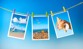 Sea pictures hanging on colorful pegs on blue background, collag Stock Images