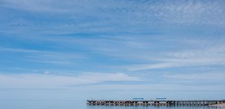 Sea pier, blue sky with light clouds stock photo