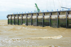Sea pier. A photo of a sea pier with murky choppy waves rolling against it Stock Photography