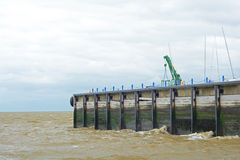Sea pier and rolling waves. A photo of a sea pier with murky choppy waves rolling against it Stock Images