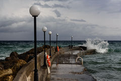 Sea pier and storm clouds Stock Photography