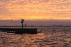 Sea pier and Tallinn cityscape on sunset Stock Photos