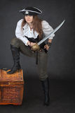 Sea pirate with sabre and chest with treasures Royalty Free Stock Image