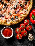 Sea pizza and tomato sauce in bowl. On dark rustic background stock photo
