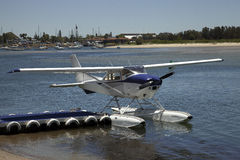 Sea Plane Float Plane Moored at the Dock of the bay. A blue and white sea plane floating at the dock in a bay with moored boats in the background Royalty Free Stock Photos