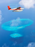 Sea plane flying above Maldives islands Stock Image