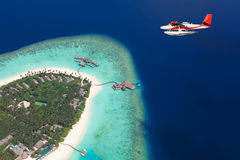 Sea plane flying above Maldives islands Stock Photos