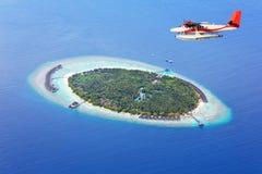 Sea plane flying above Maldives islands Stock Photos