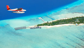 Sea plane flying above Maldives islands Stock Photo