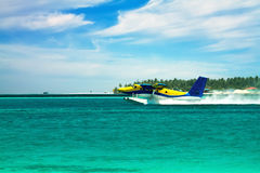Sea plane flying above ocean Stock Photos