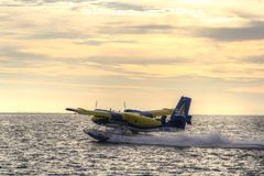 Sea plane taking off at sunset Stock Photos
