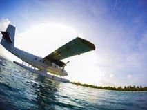 Sea plane of tropical Maldives romantic atoll island paradise lu. Silhouette of a sea plane against strong light Stock Photos