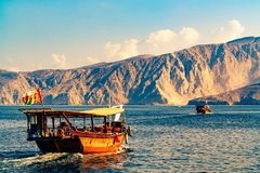 Sea, pleasure boats, rocky shores in the fjords of the Gulf of Oman stock photography