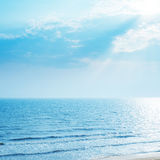 Sea with reflections and sunrays in blue sky Royalty Free Stock Photo
