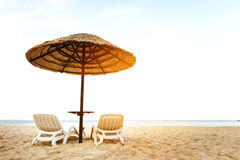 Sea resort with two chaise-longues. Under umbrella. Empty sea shore royalty free stock photo