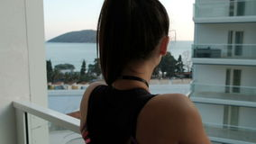 In sea resort woman back standing on the balcony of the hotel. On the open veranda brunette looks into the distance over the mountains, which are located stock video footage
