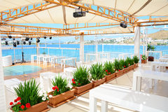 Sea restaurant with white wooden tables and sea view Royalty Free Stock Photos