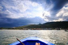 Sea Ripple Sunlight Town on Island Clouds Shadows Boat Nose Royalty Free Stock Image