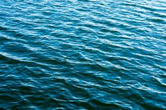 Sea ripples. Bright background. Dark green water. Shallow waves and sun glare on the water. Abstract Royalty Free Stock Photography