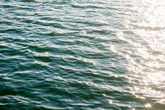 Sea ripples. Bright background. Dark green water. Shallow waves and sun glare on the water. Abstract Stock Photos