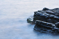 Sea and rock. Long exposure of wave in ocean royalty free stock photography