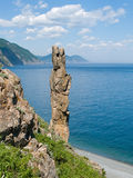 Sea and  Rock. On foreground the single vertical rock with name Hare. On background turquoise sea, cliffs and sky with white clouds. Russian Far Easr, Primorye Stock Image