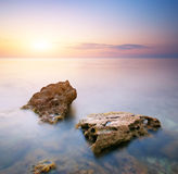 Sea and rock at the sunset Stock Photography