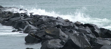 Sea Rocks. This is a line of rocks with waves crashing into them stock image