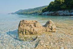 Sea rocks at calm and crystal clear turquoise water at morning, Milia beach, island of Skopelos stock photo