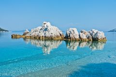 Sea rocks at calm and crystal clear turquoise water at morning, Milia beach, island of Skopelos royalty free stock photos