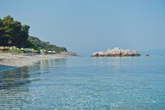 Sea rocks at calm and crystal clear turquoise water at morning, Milia beach, island of Skopelos royalty free stock photo