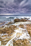 Sea, rocks and foam under a stormy sky. Royalty Free Stock Images