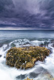 Sea, rocks and foam under a stormy sky. Royalty Free Stock Photos