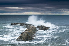 Sea, rocks and foam under a stormy sky. Stock Photo