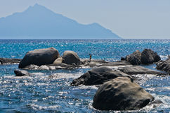Sea rocks at greek coast with holy mountain Athos in background royalty free stock photo