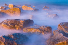 Sea rocks in haze at sunset. Scenic view of river rocks in haze at twilight Royalty Free Stock Photos