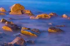 Sea rocks in haze at sunset. Scenic view of river rocks in haze at twilight Stock Image