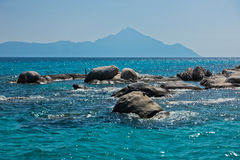 Sea rocks with holy mountain Athos in background near coast of Sithonia Stock Images