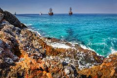 Sea and rocks landscape in tropical bay. Waves on rocky beach. Sea and mountains with ships on horizon on summer sunny day. Scenery blue sea water Royalty Free Stock Images