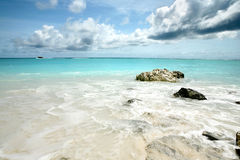 Sea rocks in Maldives with boat in distance Stock Images