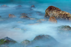 Sea rocks in mist at dusk Stock Images