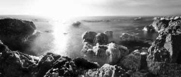 Sea Rocks on the Ocean Shore. A long exposure of ocean water between sea rocks at the beach with beautiful clouds above the horizon. Black and white infrared Royalty Free Stock Photos